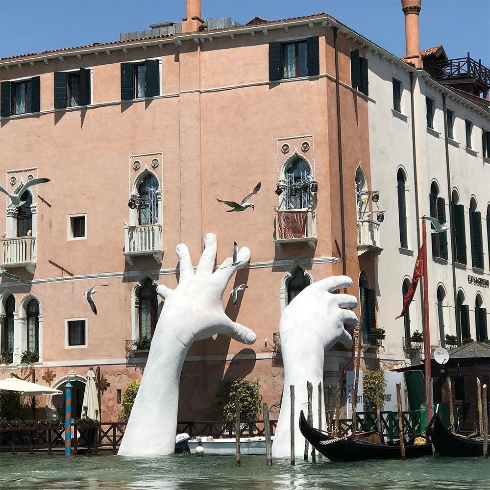 Des mains qui soutiennent les murs de Venise pour sensibiliser au réchauffement climatique