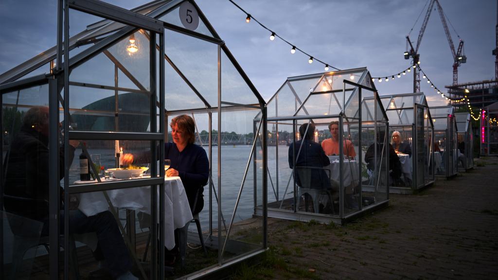 Les clients du restaurant Mediamatic à Amsterdam mangent dans des petites serres