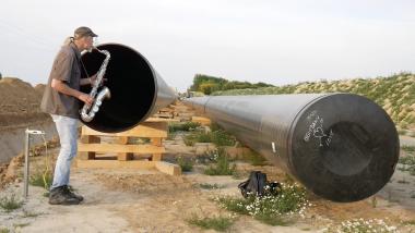 Le musicien Armin Küpper joue avec l'écho de son saxophone à l'entrée d'un pipeline