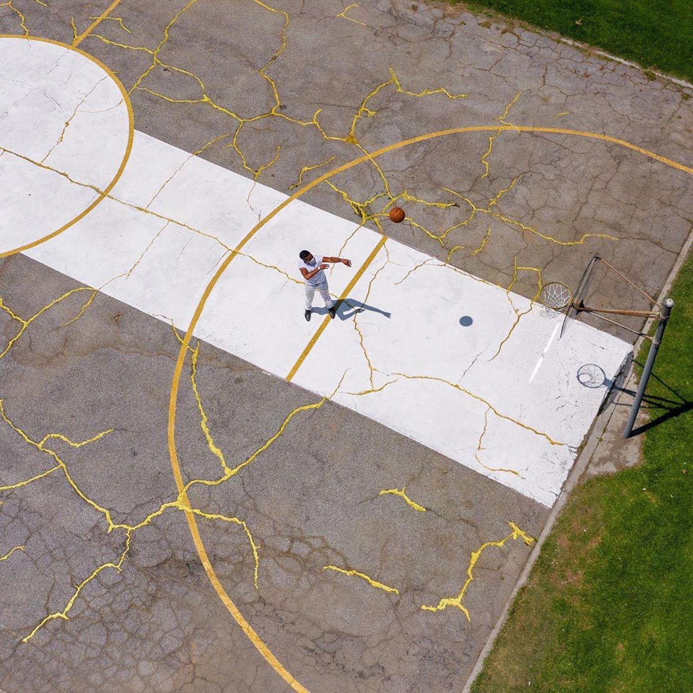 L'artiste Victor Solomon répare un terrain basket avec de la poudre d'or